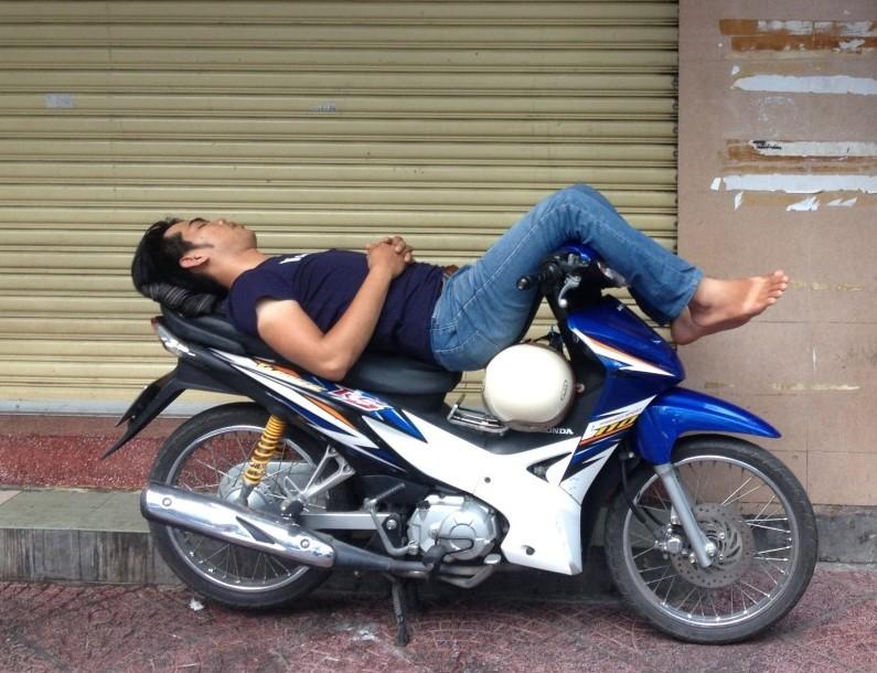 Hombre durmiendo sobre una moto.
